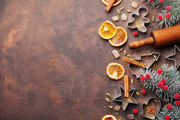 Holiday christmas background for baking cookies with cutters, rolling pin and spices on brown table top view. stock photo