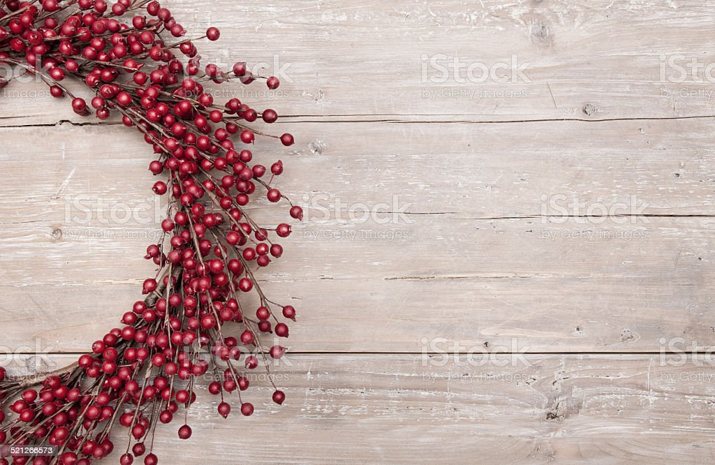 Holiday Christmas berry wreath on rustic red wood barn door stock photo