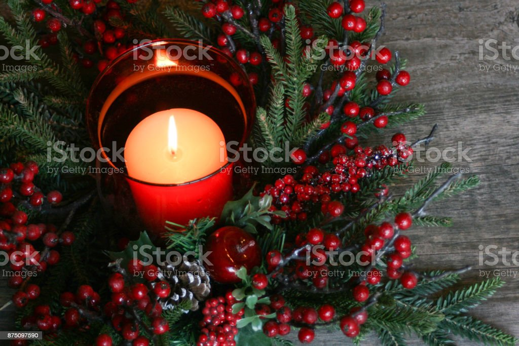 Holiday Christmas Candle with Pine Tree Branches and Berries Over...