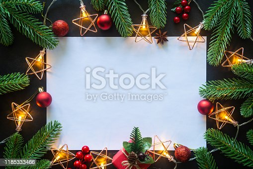 istock Holiday Christmas card background with festive decoration ball, stars, snowflakes, gift box, pine cones on a black background from Flat lay, top view. Space for text Merry Christmas and happy New Year 1185333466
