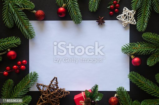 istock Holiday Christmas card background with festive decoration ball, stars, snowflakes, gift box, pine cones on a black background from Flat lay, top view. Space for text Merry Christmas and happy New Year 1185536335