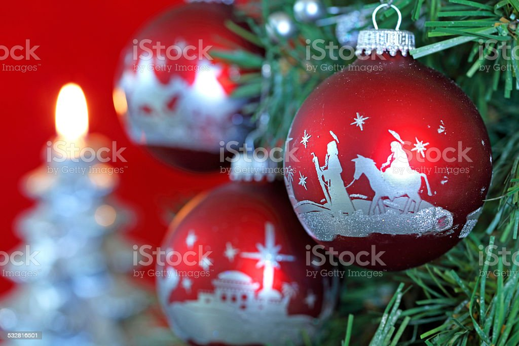 Nativity scene ornaments on a Christmas tree with a lit Christmas...