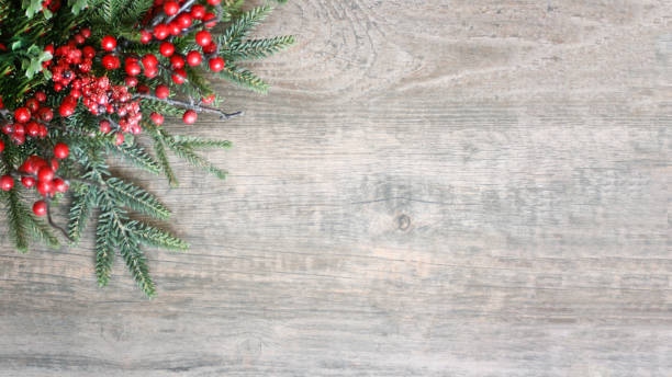 Holiday Christmas Pine Evergreen Branches and Berries Over Wood stock photo