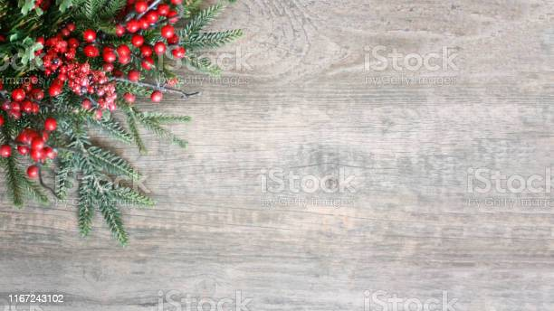 Photo of Holiday Christmas Pine Evergreen Branches and Berries Over Wood