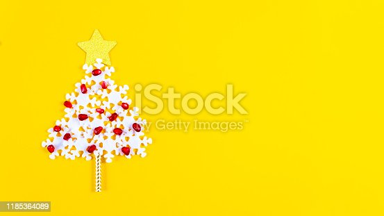 Creative xmas tree made of white snowflakes, decorated with pomegranate seeds and star on top of christmas tree. Holiday concept. Banner.
