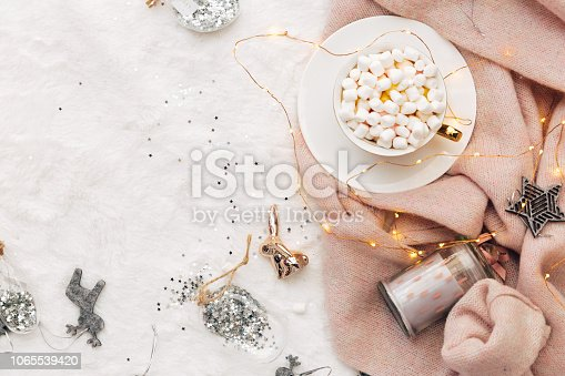 Holiday concept. Christmas composition. Cup of hot chocolate with marshmallow. Warm knitted sweater on white background. Cozy flat lay