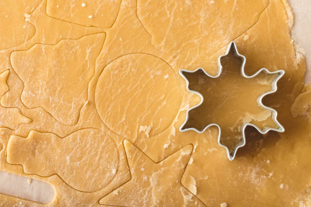 Holiday Cookie Sheet Cookies being cut from batter for Christmas cookie cutter stock pictures, royalty-free photos & images