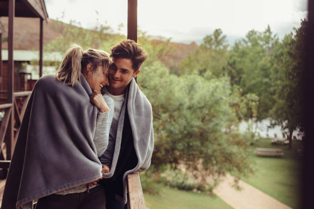 Holiday couple in hotel balcony wrapped in blanket Loving man and woman standing in their hotel room balcony wrapped in blanket. Romantic couple in a blanket standing together on a winter holiday. wrapped in a blanket stock pictures, royalty-free photos & images