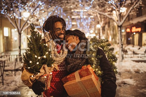 Young couple preparing for Christmas holiday. They walking on street and holding gift boxes and Christmas tree