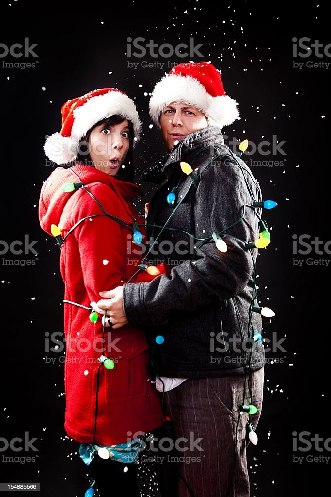 Holiday Couple Wrapped in Christmas Lights stock photo