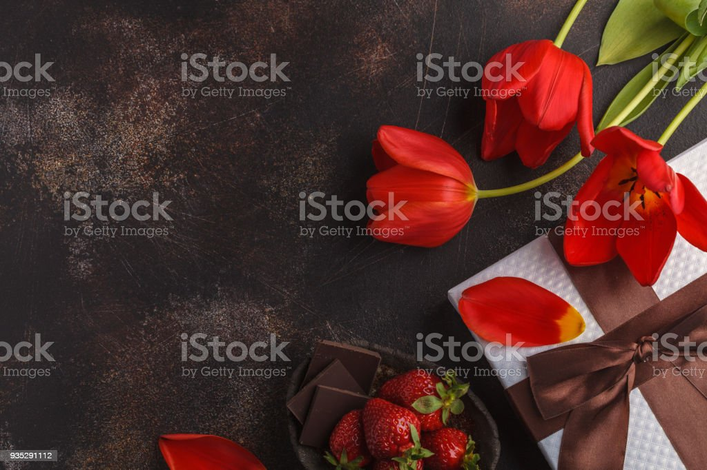 Holiday dark background. White gift box, red tulips and chocolate-strawberry dessert. Mother's Day / St. Valentine's Day / birthday concept. stock photo