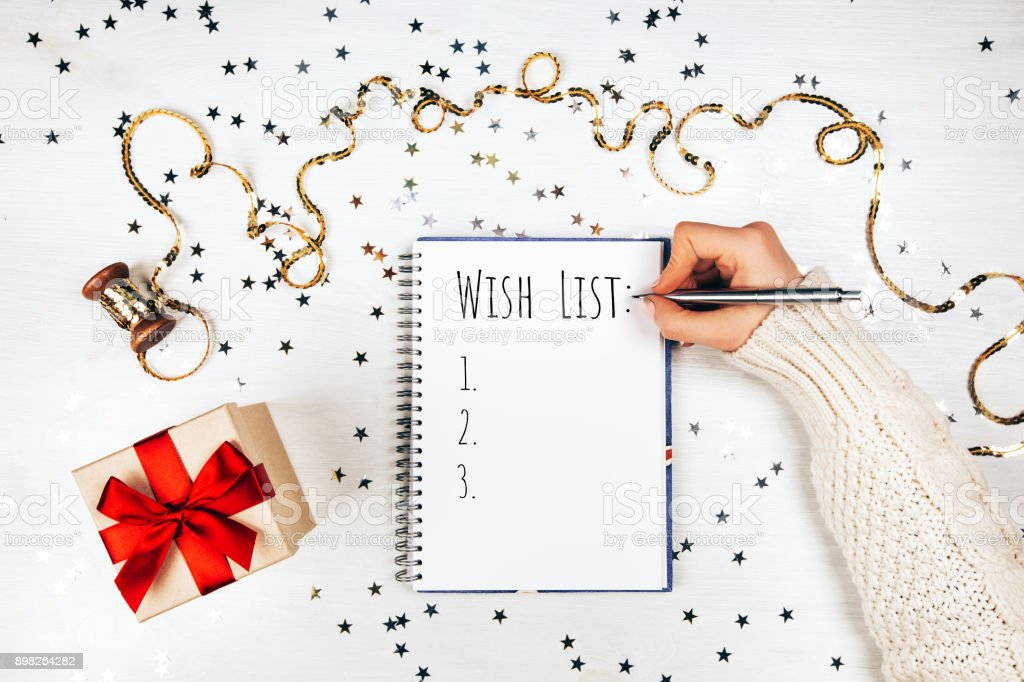 Holiday decorations and notebook with wish list on white rustic...