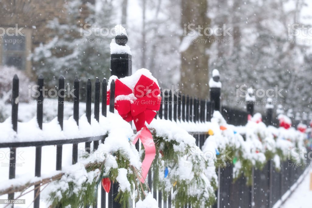Holiday decorations on fence in snow stock photo