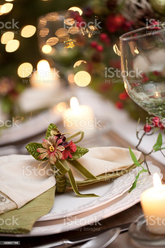 Holiday Dining Table Place Setting in Front of Christmas Tree Lights