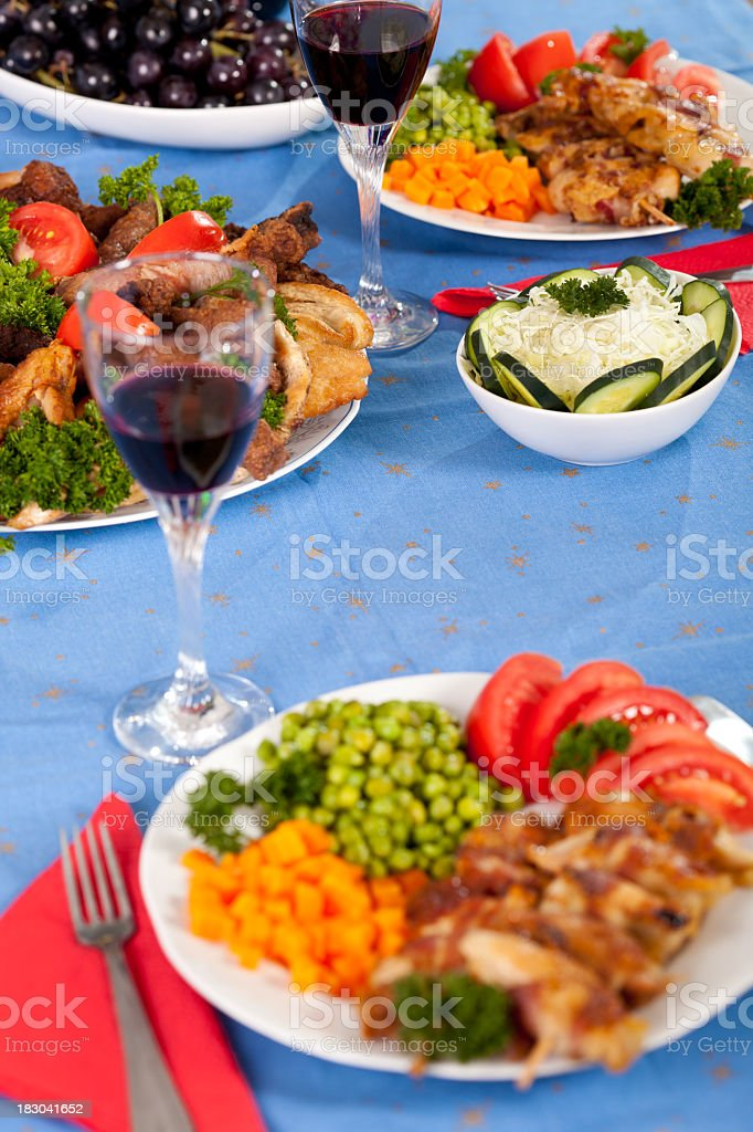 Holiday dining table with food and read wine royalty-free stock photo