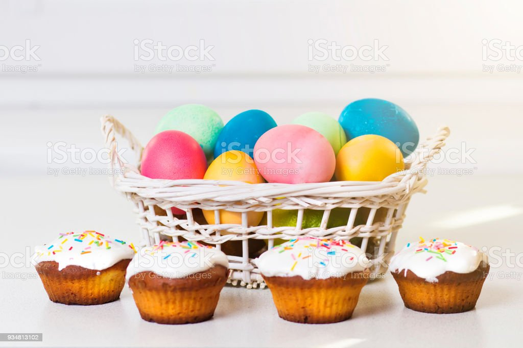 Holiday Easter concept. Multicolored easter eggs in a basket, sweet...