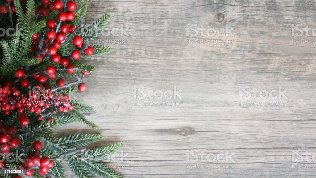 Holiday Evergreen Branches and Berries Over Wood stock photo