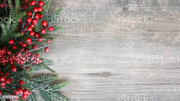 Photo of Holiday Evergreen Branches and Berries Over Wood