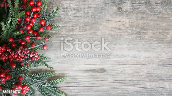 istock Holiday Evergreen Branches and Berries Over Wood 880154570