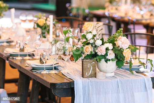 holiday, excitement, serving concept. there are untouched white dishes, clear wineglasses, silverware and gorgeous bouqets of roses avalanches on the table numbered five