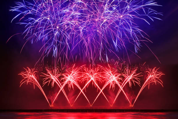 holiday fireworks of red and blue color over the water stock photo