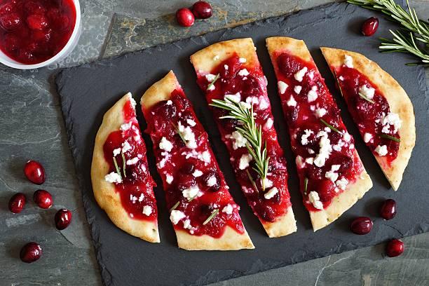 holiday flatbread appetizer with cranberries and  cheese, overhead scene - fladenbrotpizza stock-fotos und bilder
