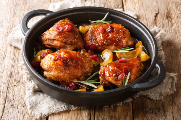 Holiday food hot baked chicken thighs with apples, cranberries and rosemary closeup in a pan. horizontal stock photo