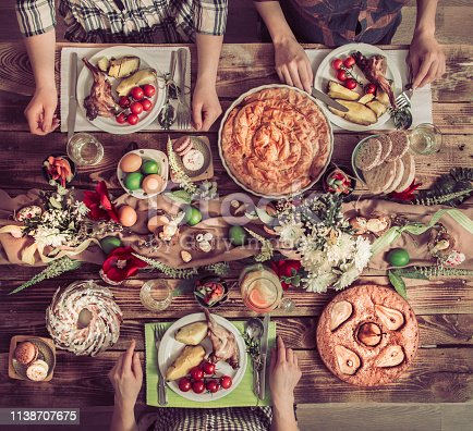 istock Holiday friends or family at the holiday table with rabbit meat, vegetables, pies, eggs, top view. 1138707675