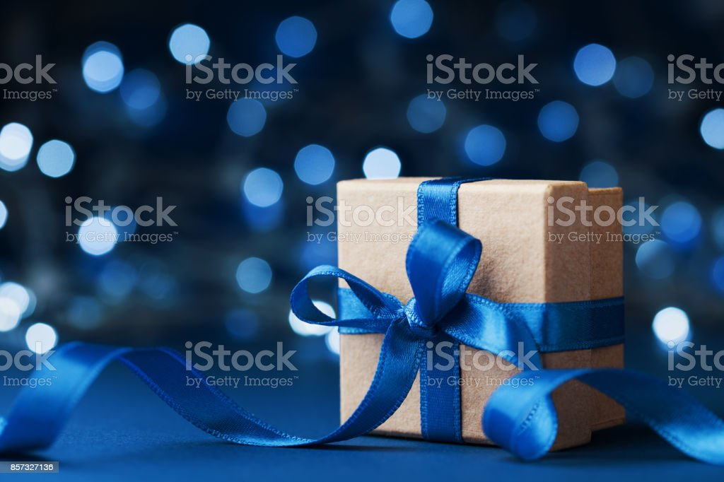 Holiday gift box or present with bow ribbon against blue bokeh background. Magic christmas greeting card. stock photo