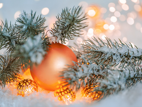 Holiday greeting card. Beautiful orange ball, pine branches and a garland in the snow. Blurred yellow bokeh background.