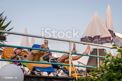 665586146istockphoto Holiday guests are sunbathing in the outdoor cafe. 1180606118