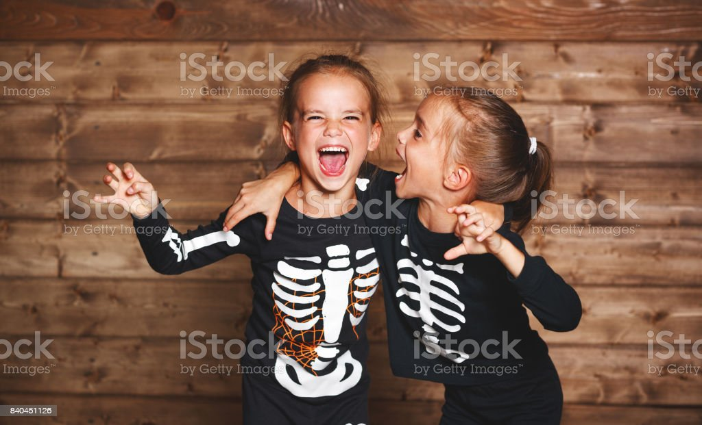holiday halloween. funny funny sisters twins children in carnival costumes skeleton  on wooden stock photo