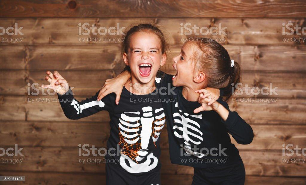 Fiesta halloween. graciosas divertidas hermanas gemelos niños en carnaval Disfraces esqueleto en madera - foto de stock