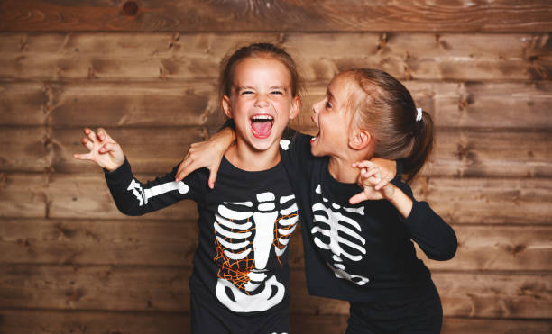 holiday halloween. funny funny sisters twins children in carnival costumes skeleton  on wooden - girls party zdjęcia i obrazy z banku zdjęć