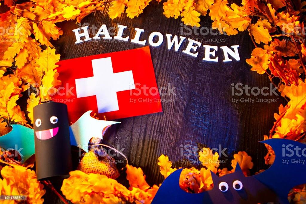 Holiday Halloween. Switzerland. Autumn holiday. Vampires against the background of yellow leaves. Decoration for the holiday of Halloween in Switzerland. the flag of Switzerland. stock photo