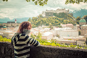 Female tourist with face mask is enjoying the view over the historic district of Salzburg