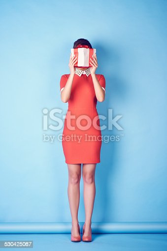 Woman hiding her face behind gift box