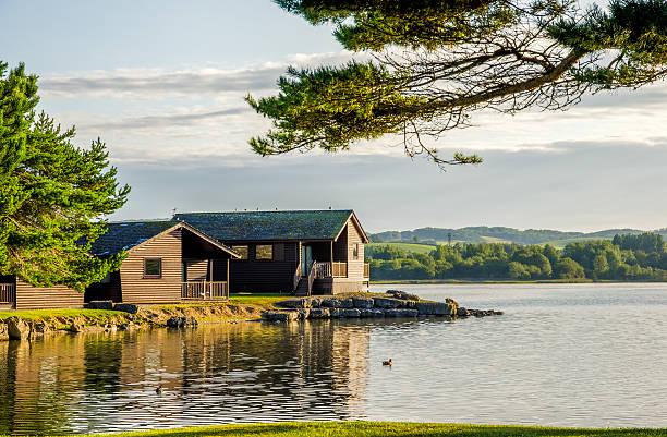 holiday lodges by a lake - kütük ev stok fotoğraflar ve resimler