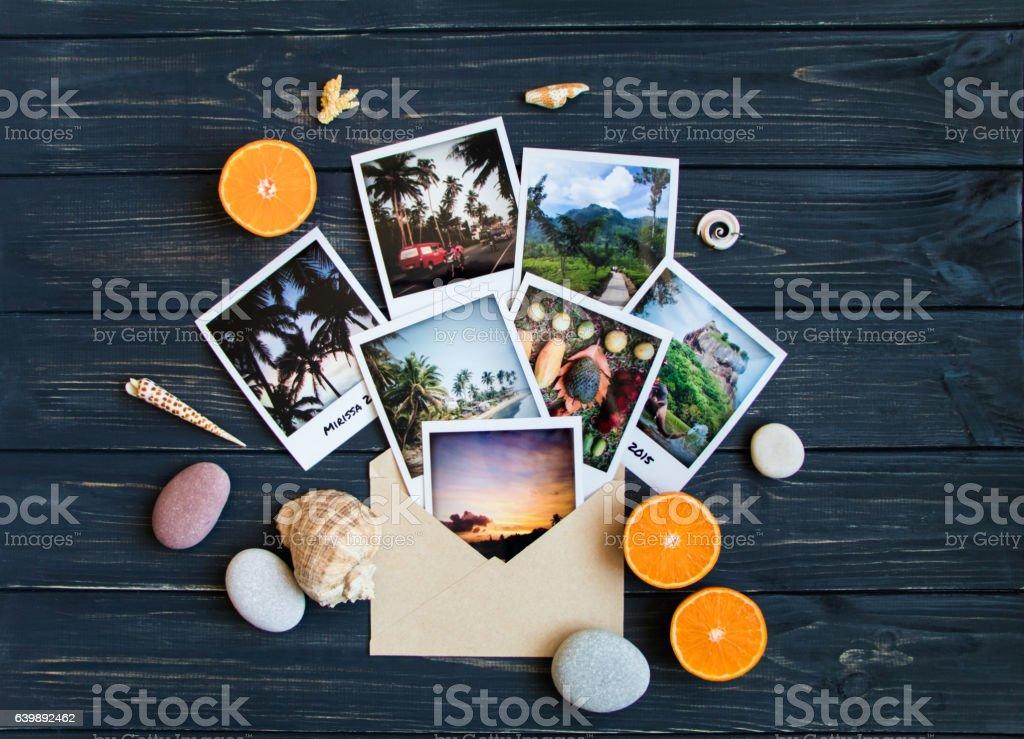 Holiday memories: photos, stones, seashells on travel photo. Flat lay stock photo