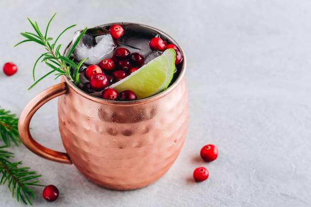 Holiday Moscow Mule ice cold Cocktail in copper cup with cranberries, lime and rosemary on stone background. Holiday Moscow Mule ice cold Cocktail in copper cup with cranberries, lime and rosemary on gray stone background. mule stock pictures, royalty-free photos & images
