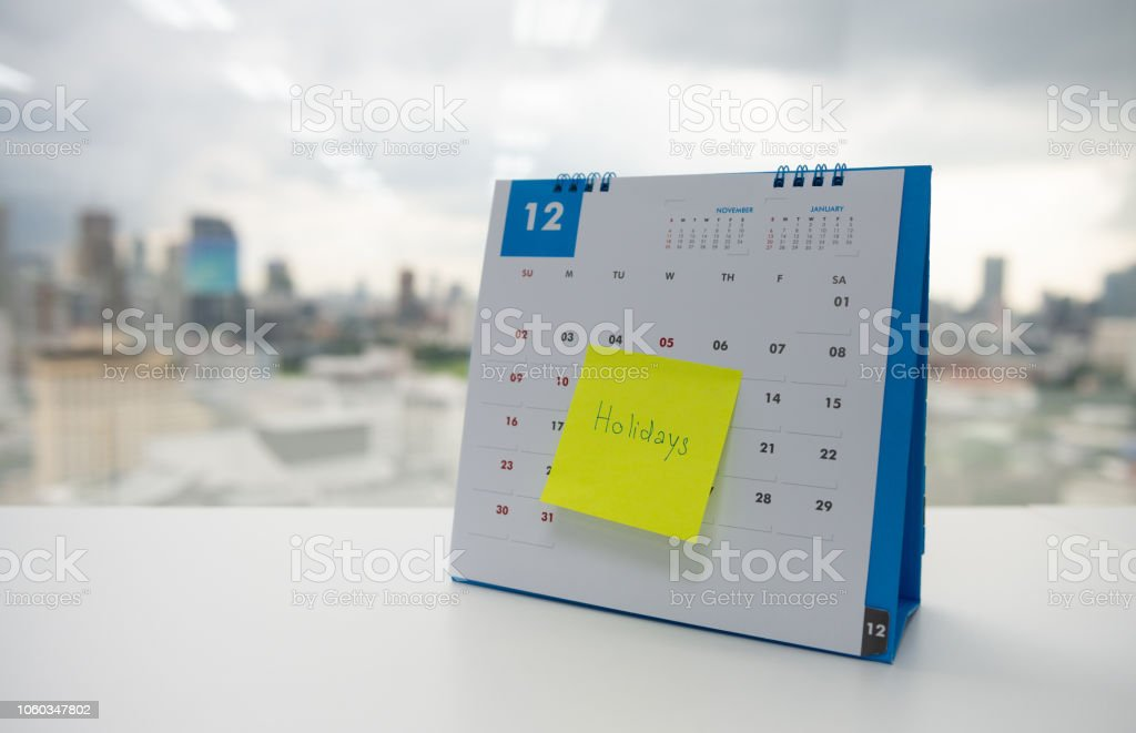 Holiday on paper note stick on the calendar of December for year end holidays concept stock photo