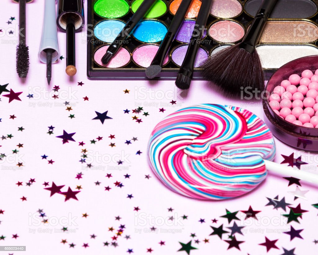 Holiday party makeup cosmetics with lollipop and confetti stock photo