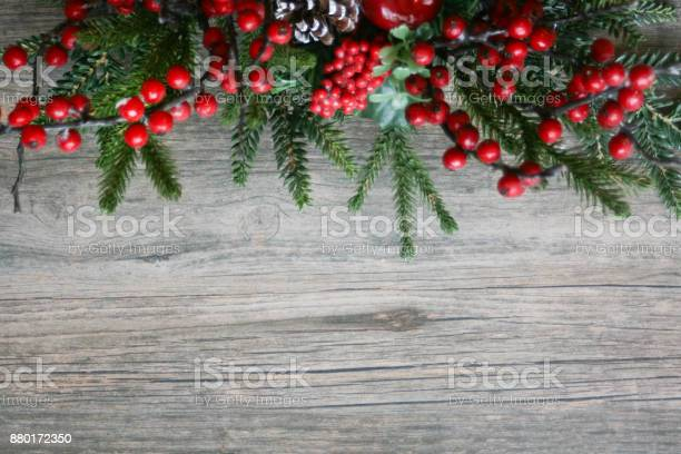Photo of Holiday Pine Branches and Berries Over Wood Horizontal Background