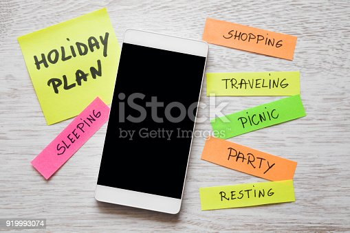 istock Holiday planning. Colorful paper sheets with written different goals on desk. Plans about party, shopping, resting, traveling and other. To do list concept. Empty place for text on the black screen. 919993074