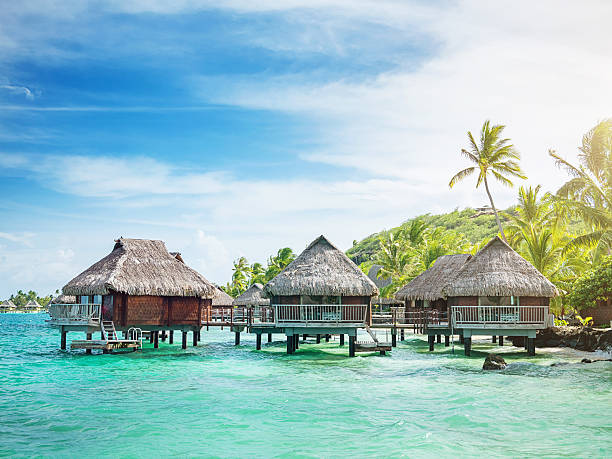 Holiday Resort in Ocean French Polynesia Bora Bora. View over beautiful turquoise lagoon and amazing hotel resort in the sun. Bora Bora Island, Society Islands, French Polynesia. south pacific ocean stock pictures, royalty-free photos & images
