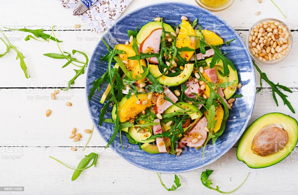 Holiday salad with smoked chicken, mango, avocado and arugula. Flat lay. Top view stock photo