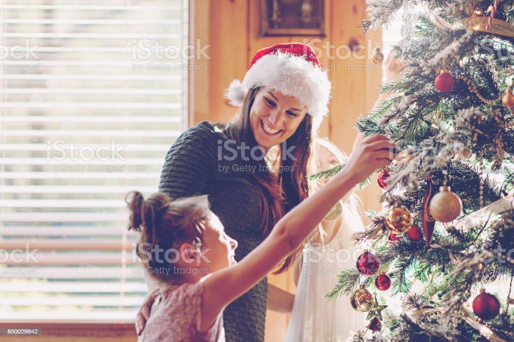 Holiday Season : Family decorating the christmas tree stock photo