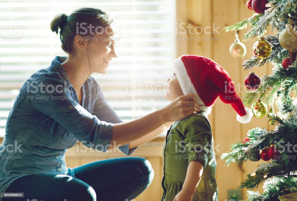 Holiday Season : Family decorating the christmas tree stock photo