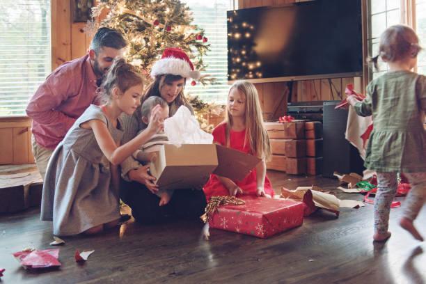ferienzeit: familie schmücken den weihnachtsbaum - geschenke eltern weihnachten stock-fotos und bilder