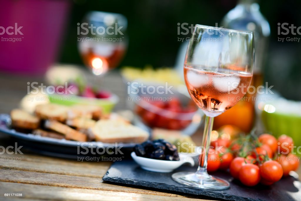 holiday summer brunch party table outdoor in a house backyard with appetizer, glass of rosé wine, fresh drink and organic vegetables stock photo